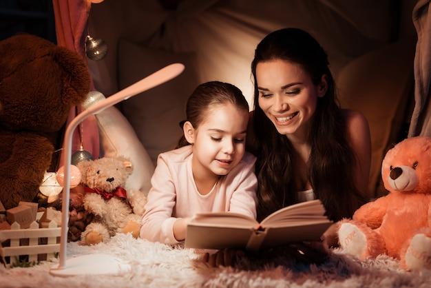 Mutter und tochter lesen buch im haus.