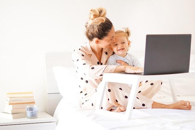 Mutter und tochter liegen im schlafanzug im bett und lächeln sich an