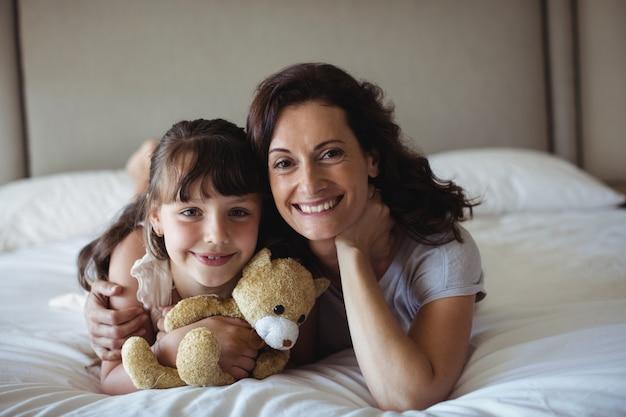 Mutter und tochter liegen mit teddybär im schlafzimmer auf dem bett