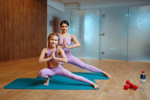 Mutter und tochter machen gleichgewichtsübungen auf matten im fitnessstudio, yoga-training. mutter und kleines mädchen in sportkleidung, gemeinsames training im sportclub