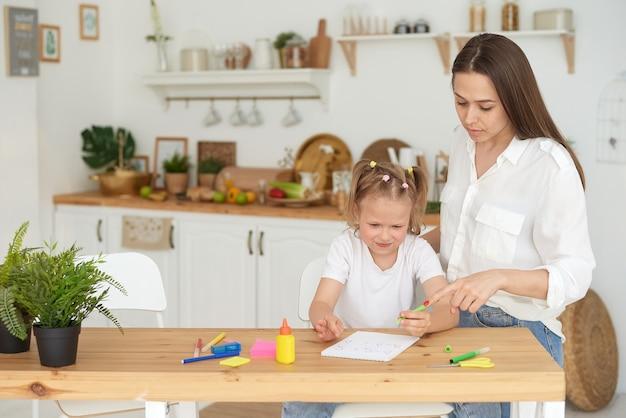 Mutter und tochter machen hausaufgaben. ein kleines mädchen erledigt unter der aufsicht eines tutors nachdenklich mathematische aufgaben. das konzept, auf ein kind aufzupassen und bei den hausaufgaben zu helfen.