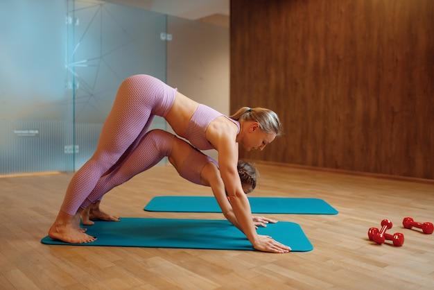Mutter und tochter machen presseübung auf matten im fitnessstudio, yoga-training. mutter und kleines mädchen in sportbekleidung, frau mit kind, gemeinsames training im sportclub