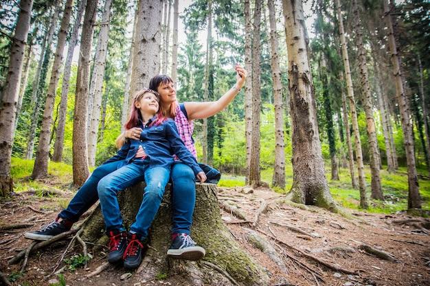 Mutter und tochter machen selfie sitzen auf dem baumstamm in einem wald