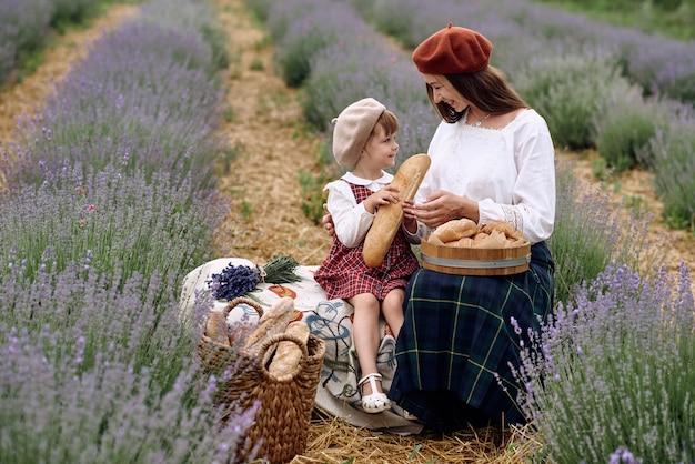 Mutter und tochter machten ein picknick in einem lavendelfeld.