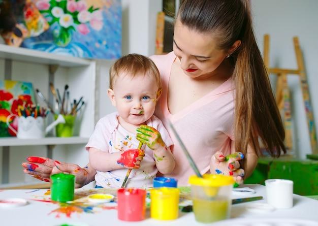Mutter und tochter malen auf leinwand in der zeichenschule.