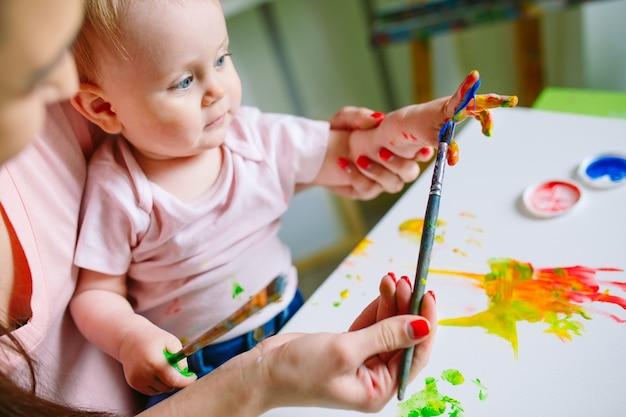 Mutter und tochter malen auf leinwand in der zeichenschule