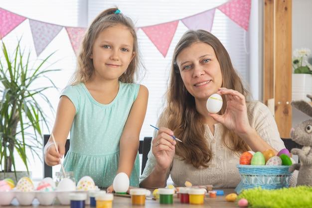 Mutter und tochter malen eier für den hellen osterfeiertag. sitzen sie glücklich mit farben