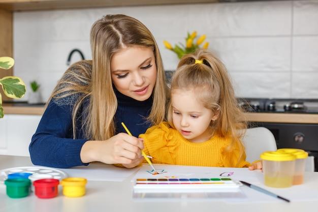 Mutter und tochter malen zu hause. kind, das spaß hat. frühkindliche bildung, freizeit im vorschulalter