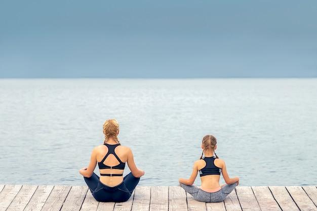 Mutter und tochter meditieren am pier am meer
