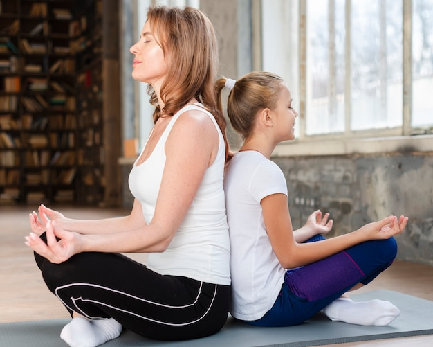 Mutter und tochter meditieren rücken an rücken auf yogamatten