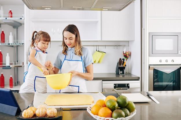 Mutter und tochter mischen zuckerguss in einer großen plastikschüssel, bevor sie ihn auf gebackenen kuchen legen