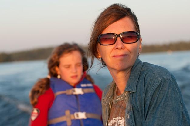 Mutter und tochter mit dem sonnenlicht in ihrem gesicht beim reiten in ein boot am see des holzes, ontario