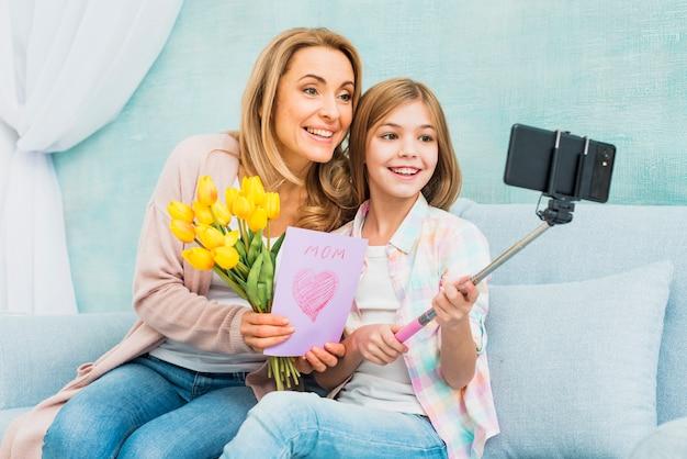 Mutter und tochter mit den geschenken, die selfie nehmen