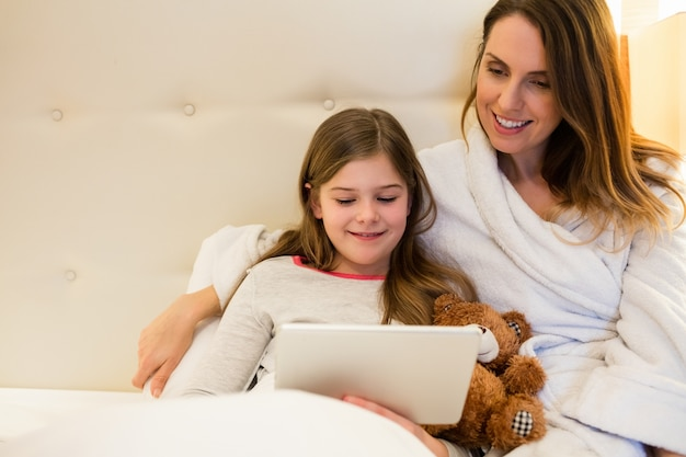 Mutter und tochter mit der digitalen tablette im schlafzimmer