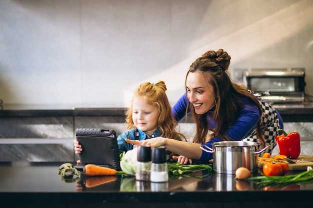 Mutter und tochter mit der tablette, die in der küche kocht