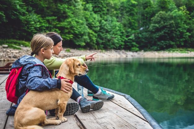 Mutter und tochter mit einem hund, der auf einem pier stillsteht