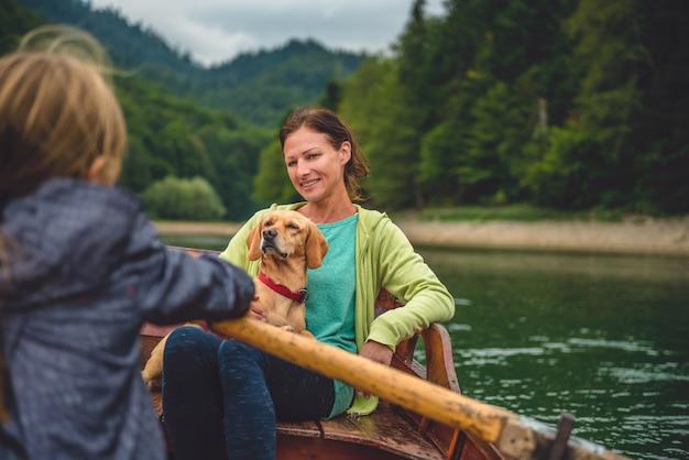 Mutter und tochter mit einem hund, der ein boot rudert