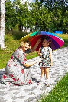 Mutter und tochter mit einem regenbogenregenschirm, die an einem sonnigen sommertag im park spazieren gehen
