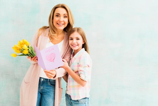 Mutter und tochter mit geschenken lächelnd und kamera betrachten