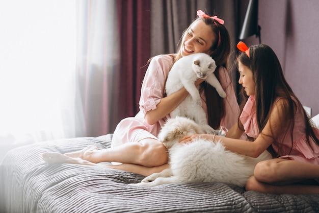 Mutter und tochter mit kätzchen und hund