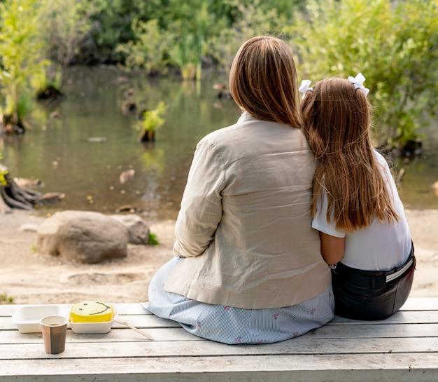 Mutter und tochter mit kuchen auf einer bank im park