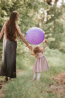 Mutter und tochter mit luftballons. schöne glückliche mutter mit der tochter, die spaß auf dem grünen gebiet hält ballone hat. mama, kind, mutter.