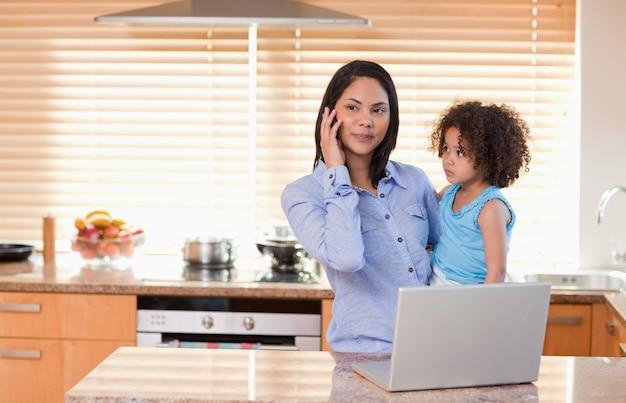 Mutter und tochter mit mobiltelefon und laptop in der küche zusammen