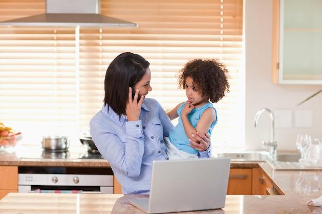 Mutter und tochter mit mobiltelefon und notizbuch in der küche zusammen