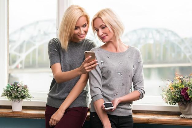 Mutter und tochter mit smartphones
