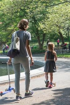 Mutter und tochter mit stoßroller im central park, manhattan, new york city, staat new york, usa