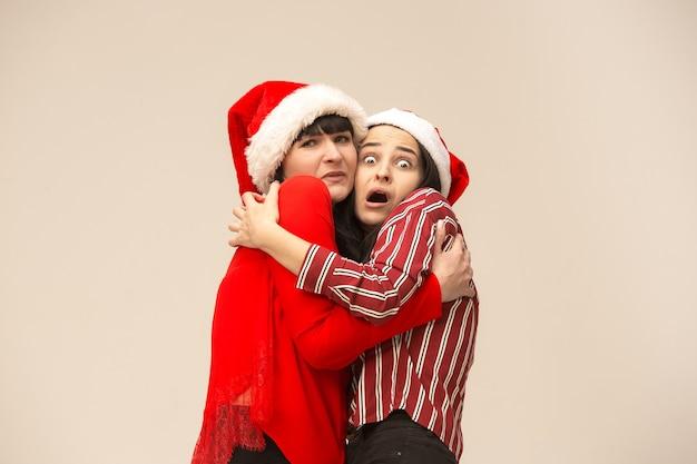 Mutter und tochter mit weihnachtsmütze. emotionaler ausdruck.