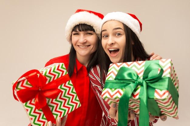Mutter und tochter mit weihnachtsmütze und geschenkbox