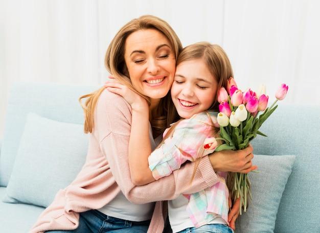Mutter und tochter mit zufriedenem gesicht umarmen