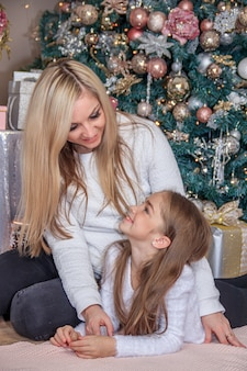 Mutter und tochter neben dem weihnachtsbaum. urlaub neujahr und weihnachten. schöne mutter und tochter.