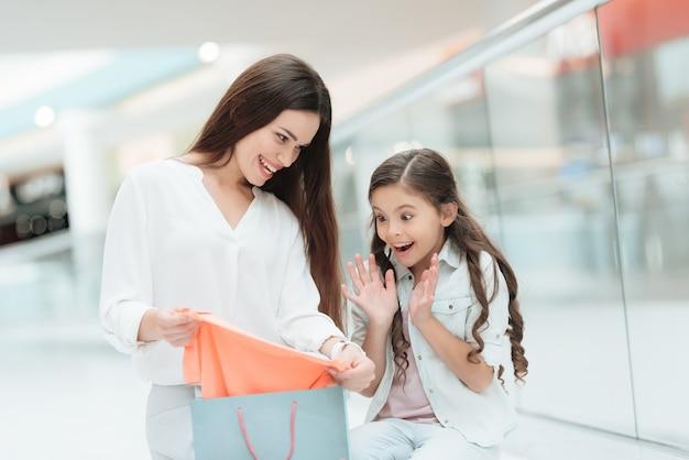 Mutter und tochter nehmen aus einkaufstasche heraus.
