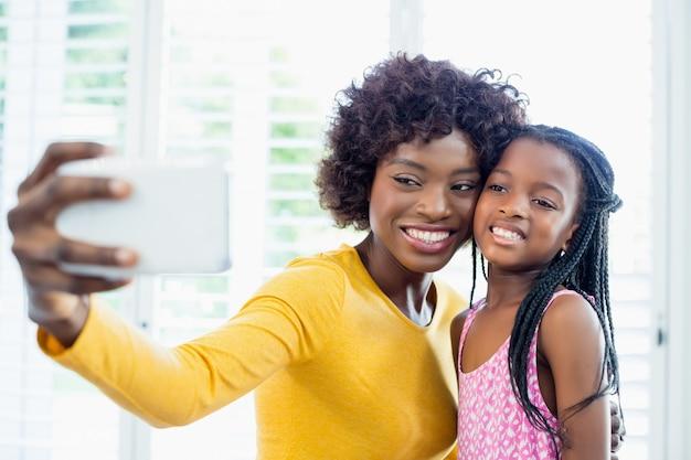Mutter und tochter nehmen ein selfie vom handy im wohnzimmer