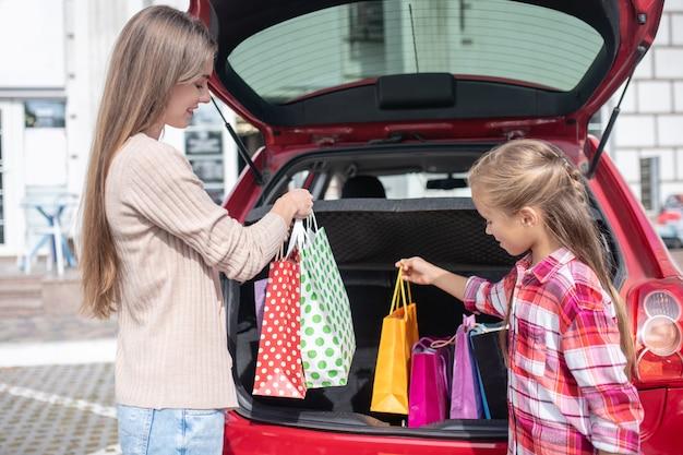 Mutter und tochter nehmen einkaufstaschen aus dem kofferraum