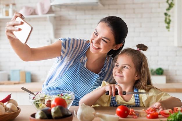 Mutter und tochter nehmen selfie in der küche