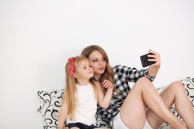 Mutter und tochter nehmen selfie, während sie zu hause auf dem bett ruhen