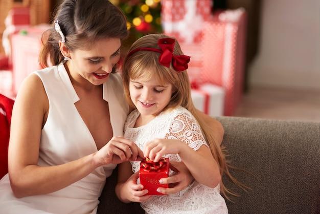 Mutter und tochter öffnen verpacktes geschenk