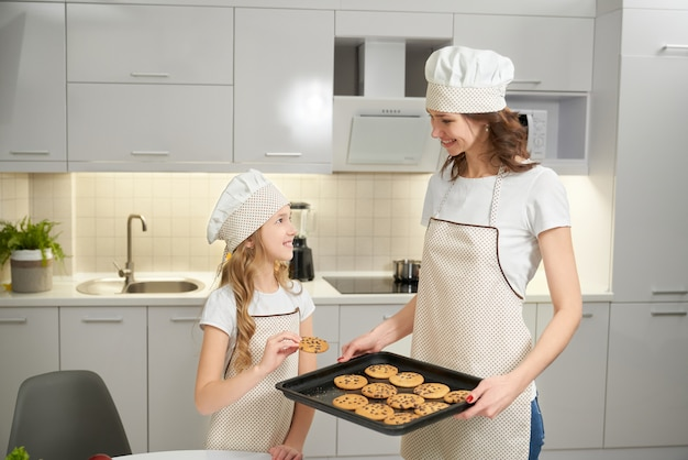 Mutter und tochter posieren mit backblech und keksen.