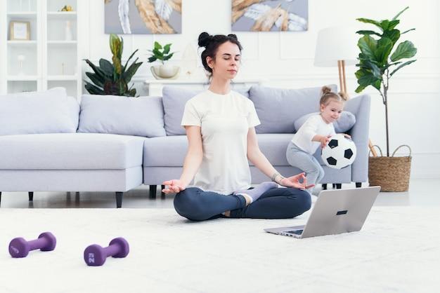 Mutter und tochter praktizieren online-yoga-unterricht zu hause in der quarantäne-isolationsphase während der coronavirus-pandemie. familie, die zusammen online von zu hause aus sport treibt. gesunder lebensstil