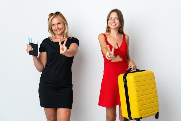 Mutter und tochter reisen isoliert auf weiß lächelnd und zeigen siegeszeichen