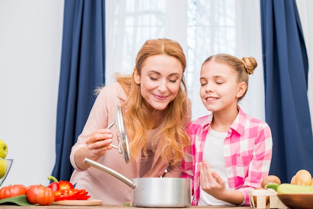 Mutter und tochter riechen das zubereitete essen in der küche