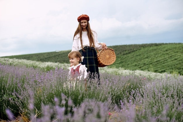 Mutter und tochter sammeln zusammen lavendelblüten in einem korb.