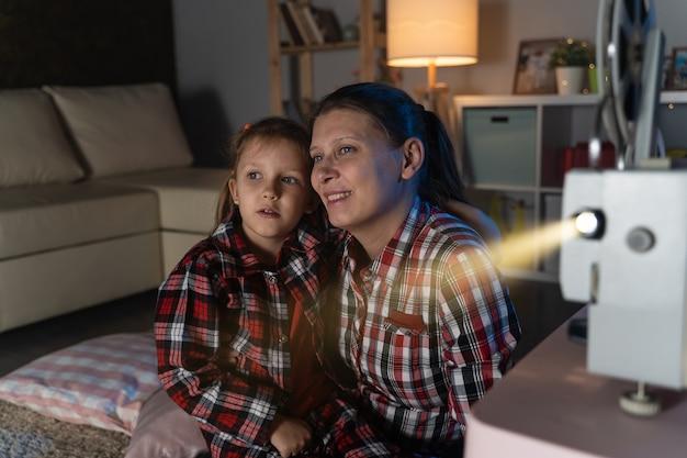 Mutter und tochter schauen alten film auf retro-vintage-filmprojektor zu hause