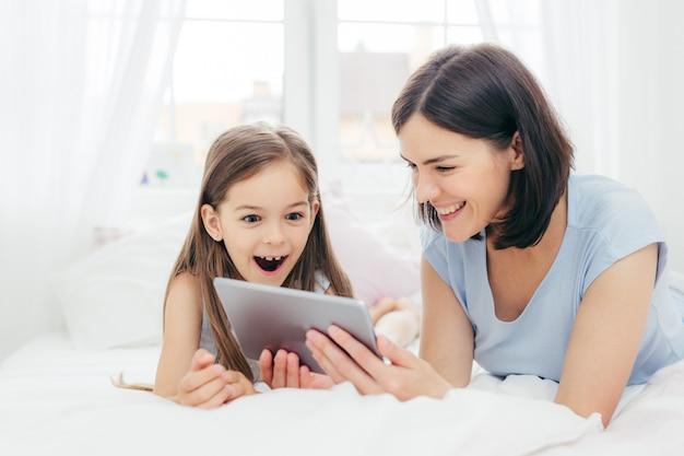 Mutter und tochter schauen sich etwas lustiges auf dem tablet-computer an