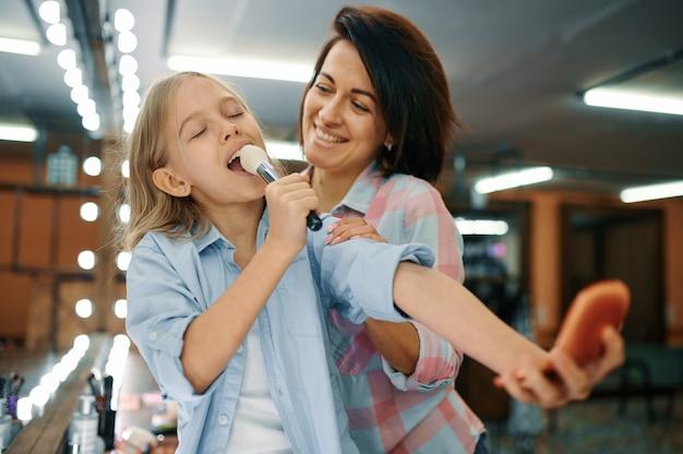 Mutter und tochter scherzen im make-up-salon