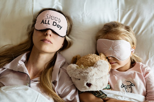 Mutter und tochter schlafen mit verbundenen augen auf dem bett