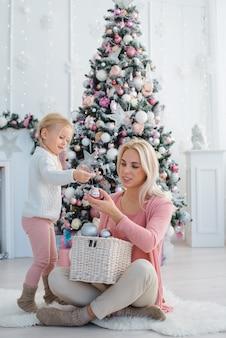 Mutter und tochter schmücken den weihnachtsbaum rosa drinnen